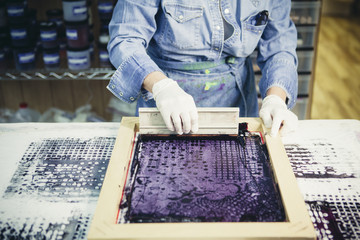 Midsection of craftswoman using silk screen to print design on fabric at workshop