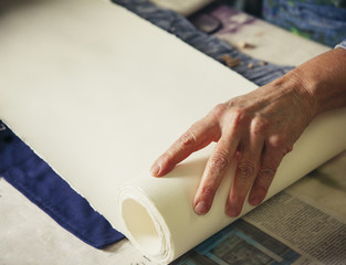 Cropped hands of craftswoman adjusting rolled up paper on fabric at workshop