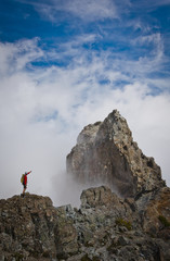 High angle view of hiker pointing towards mountain while standing on rock amidst clouds