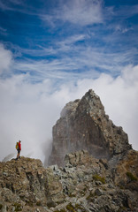 High angle view of hiker standing on mountain amidst clouds