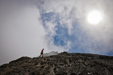 Low angle view of hiker climbing rock formations against cloudy sky