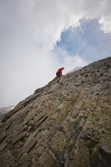 Low angle view of determined hiker climbing rock formations against cloudy sky