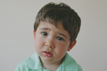 Close-up portrait of sad baby boy against gray background