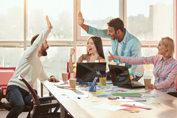 Casual colleagues doing high-five in the office. Students rejoice at the performance of work.
