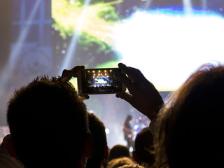 Concert fans filming the stage with a smart phone