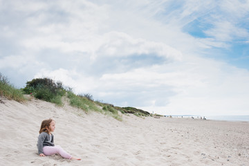 little girl sitting on a beach watching the sea