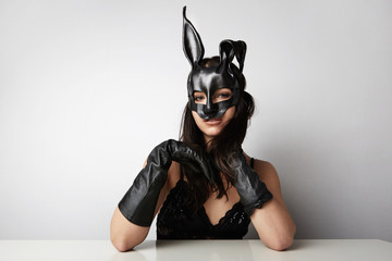 Sexy woman wearing a black mask Easter bunny standing on a white background
