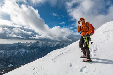 Mountaineer photographing on the snowy slope of the Dovska Baba mountain in Karavanke range, Slovenia