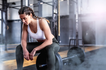 Shot of fitness woman in gym with barbell