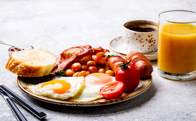 Traditional English Breakfast Food on stone Eggs ,Sausages, Bacon, Beans,Toasts,Coffe and Orange juice
