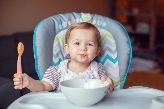 Portrait of cute adorable Caucasian child kid girl sitting in high chair eating cereal with spoon. Everyday lifestyle. Candid real authentic moment