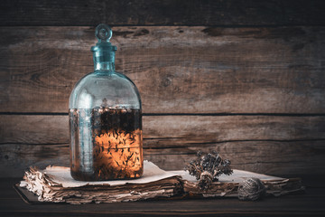 Tincture or potion bottle, old book and bunch of dry healthy herbs. Herbal medicine. Retro styled.