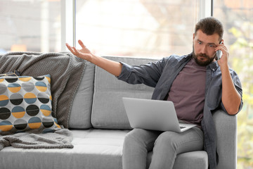 Emotional man with laptop talking on phone at home
