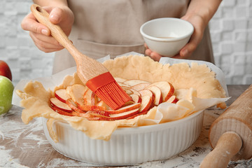 Woman preparing apple tart in kitchen