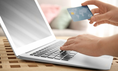 Woman holding credit card while using laptop, closeup. Internet shopping concept