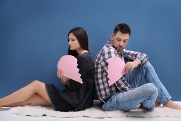 Young couple holding paper heart cut in half near color wall. Relationship problems