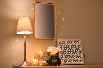 Modern mirror with garland on wall over table