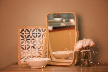 Beautiful modern mirror as decorative element on table