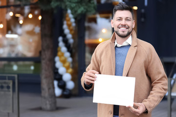Business owner holding blank paper near his store