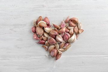 Heart shape of fresh garlic on white wooden background