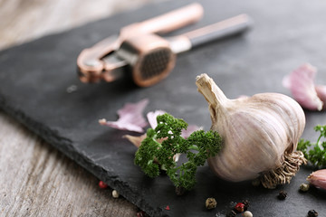 Fresh garlic with spices on slate plate