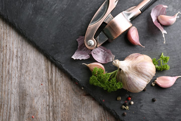 Fresh garlic with spices and crusher on slate plate
