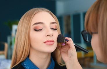 Professional visage artist applying makeup on woman's face backstage