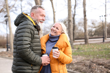 Happy mature couple with coffee outdoors