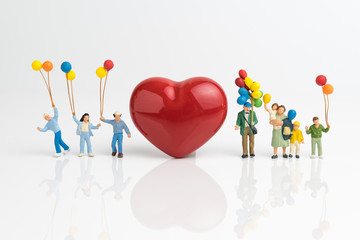 Happy Valentine's day card or wallpaper concept, miniature people happy love family holding balloons with red heart shape on white background