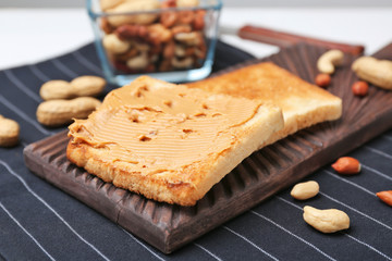 Wooden board with toasted bread on table