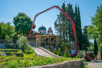 BOSNIA AND HERZEGOVINA, TVRDOS MONASTERY - JUNE 01/2017: workers use a special pump to pour concrete for construction.