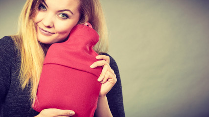 Woman hugs hot water bottle in red fleece cover