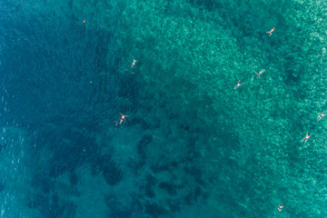 Aerial view of the turquoise sea surface in which people bathe