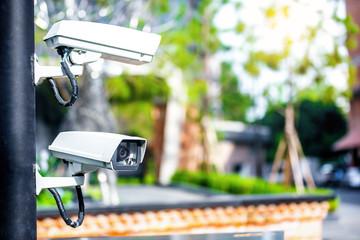 two CCTV security surveillance cameras out door in garden park