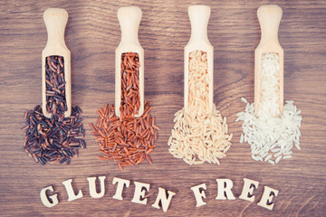 Vintage photo, Black, red, brown and white rice on wooden scoop on rustic board, healthy food concept