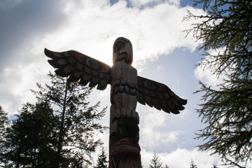 Silhouette of wooden totem pole against a summer sky