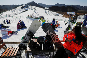 Members of staff and visitors get ready to ski down the slope at Nanshan ski resort, east of Beijing