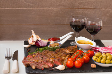 Appetizing grilled meat. Grilled beef entrecote medium roast on black stone board, red wine and two full wine glasses. Best dinner.