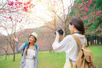 woman using camera helping friend taking picture