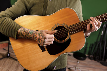 Closeup of unrecognizable tattooed man playing acoustic guitar in recording studio