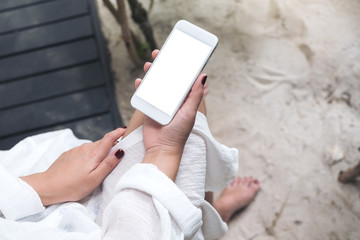 Mockup image of a woman's hand holding white mobile phone with blank desktop screen with sand and beach background