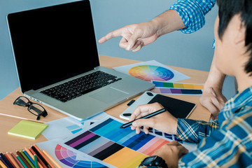Designer graphic creative ,Man pointing Working on laptop in office with sunset background,Selective focus.