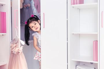 Lovely little girl hide and seek in the bedroom