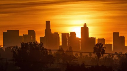 Fototapete - Sunrise sun rising behind downtown Los Angeles skyscrapers, beautiful city skyline. 4K UHD timelapse.