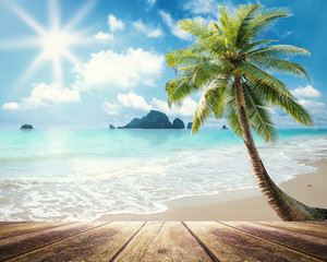 Summer holiday concept: Wooden table with coconut palm tree at the beach background.