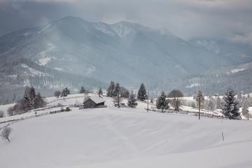 winter in the mountains - small Romanian village in the Carpathians covered with snow