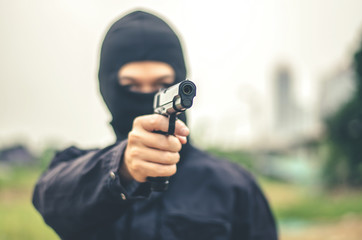 Mask thief in balaclava with holding gun ,Outlaw bad man  hold a gun pointing the target , robber in black hood holding gun and pointing to victim