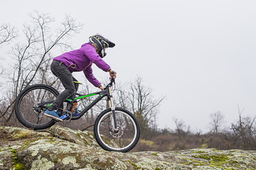 Enduro Cyclist Riding the Mountain Bike on the Rocky Trail, copy of free space.