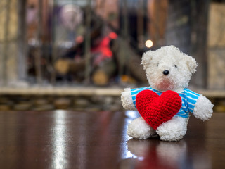 White teddy bear wearing blue shirt Hold red heart and sitting on the wood table in front of the fireplace copy space for text. romantic, warm and Valentines day, love concept and love background