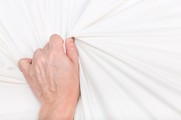 hand of men pulling white sheets in ecstasy, orgasm